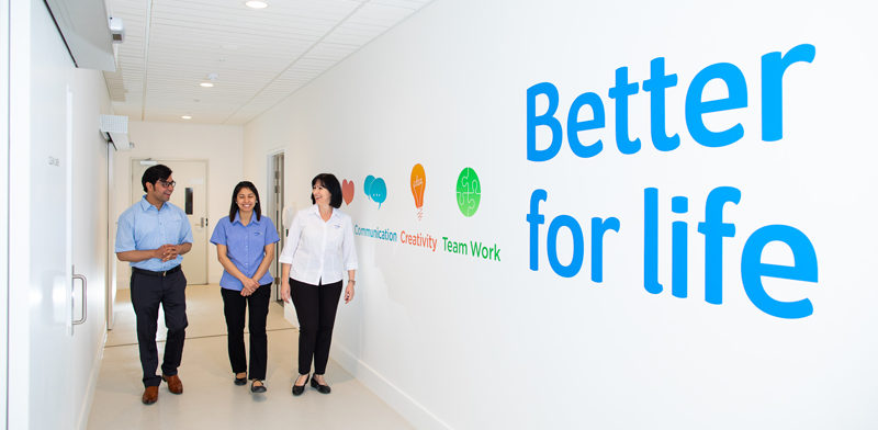 A man and two women are walking along a corridor that has the words 'Better for life' on the right.