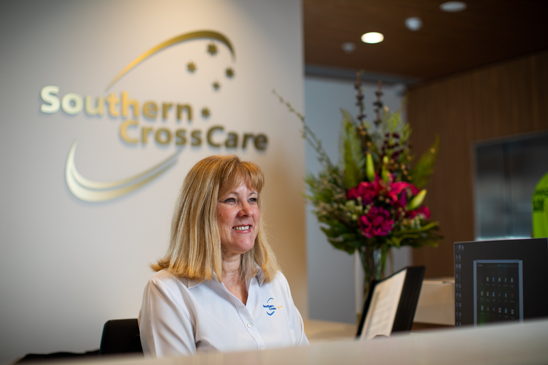 There is a woman at the receptionist counter. Above her are the words 'Southern Cross Care""